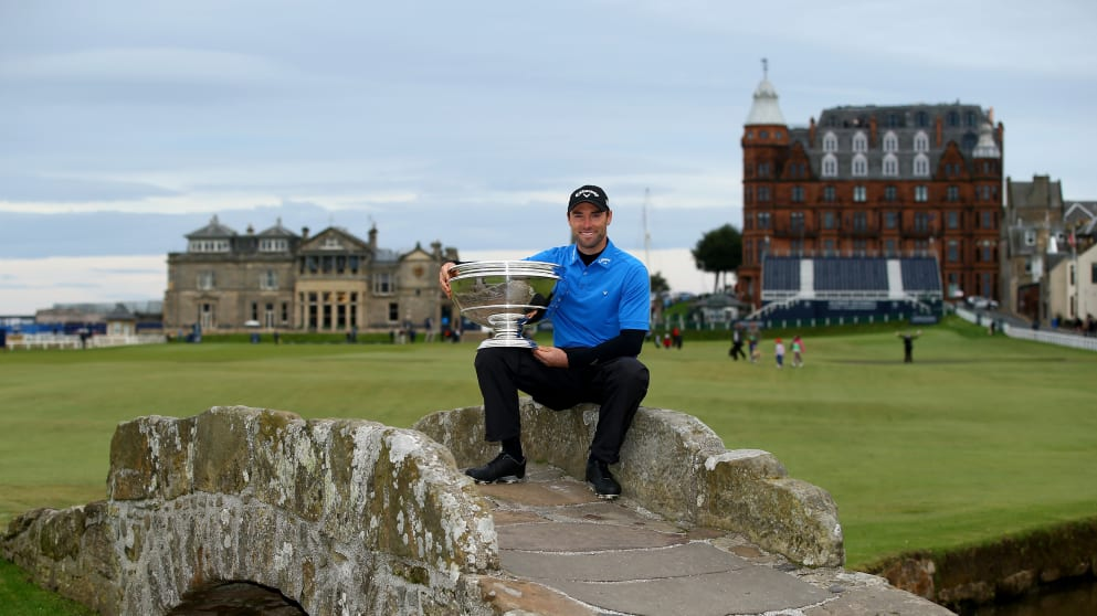 Oliver Wilson holds the trophy aloft on the Swilcan Bridge at St Andrews